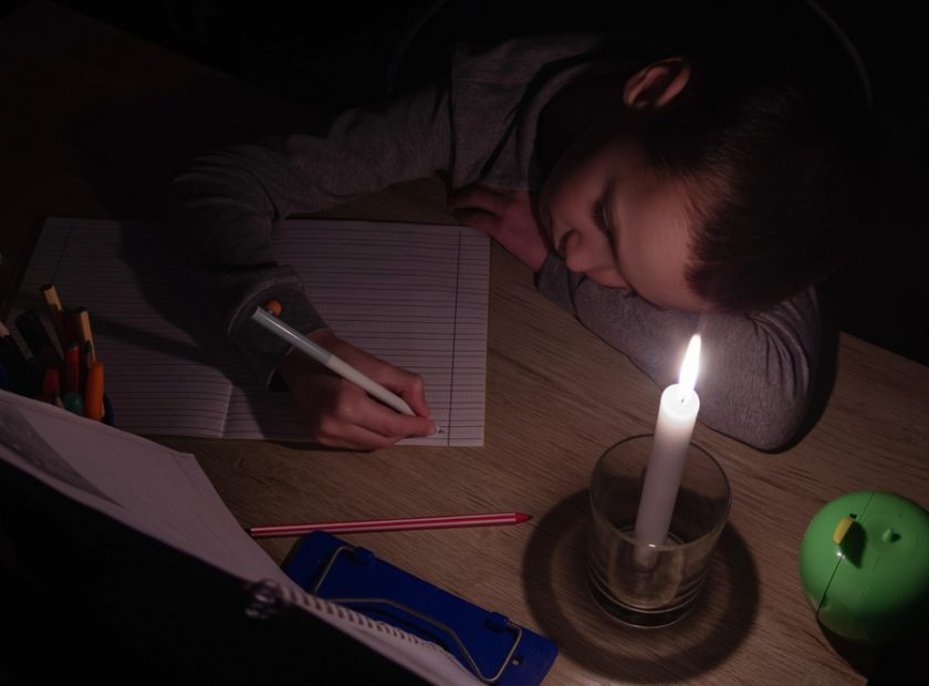 Tired,Schoolboy,With,Candle,In,Complete,Darkness,Doing,Homework.,Power