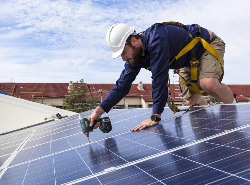 Solar,Panel,Technician,With,Drill,Installing,Solar,Panels,On,Roof